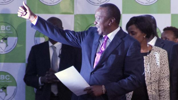 Uhuru Kenyatte im Anzug streckt Arm mit nach oben gestrecktem Daumen.
