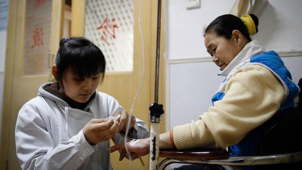 Immer häufiger werden chinesische Ärzte von Patienten oder ihren Familien angegriffen. Grund dafür sind Mängel im Gesundheitswesen.Bild: Eine Krankenschwester behandelt eine Patientin in einer Klinik in Peking.