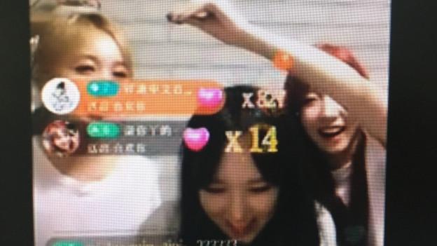 Drei junge Frauen, eine blond, eine dunkel und eine rothaarig, vor einem Geburtstagskuchen, im Vordergrund chinesische Chatnachrichten.