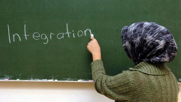 Auf dem Bild zu sehen ist eine Muslimin, die das Wort Integration auf eine Wandtafel schreibt