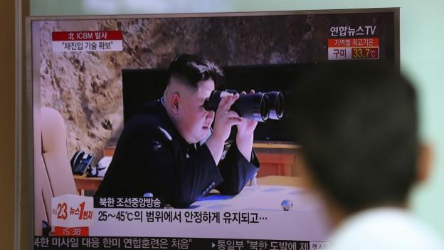 Auf dem Bild zu sehen ist der nordkoreanische Machthaber, der mit einem Feldstecher einen Raketentest beobachtet