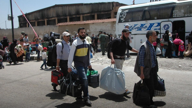 Menschen stehen mit viel Gepäck vor Büssen.