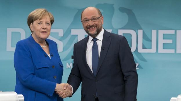 Merkel und Schulz geben sich die Hand.