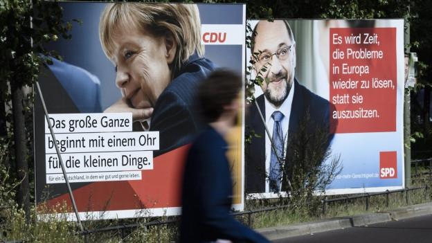 Das Wahlplakat von Angela Merkel neben einem Wahlplakat von Martin Schulz.