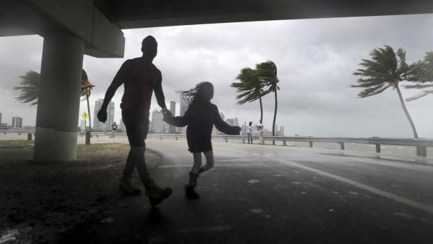 Zwei Leute überqueren die Straße in Miami während der Hurrikan Irma sich am Wochenende nähert.
