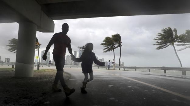 Auf dem Bild zu sehen sind ein Mann und ein Mädchen, welche sich durch den Regen und den Wind kämpfen