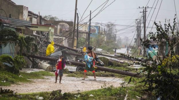 Einwohner laufen durch Strassen, über die Stromleitungen kreuz und quer liegen.