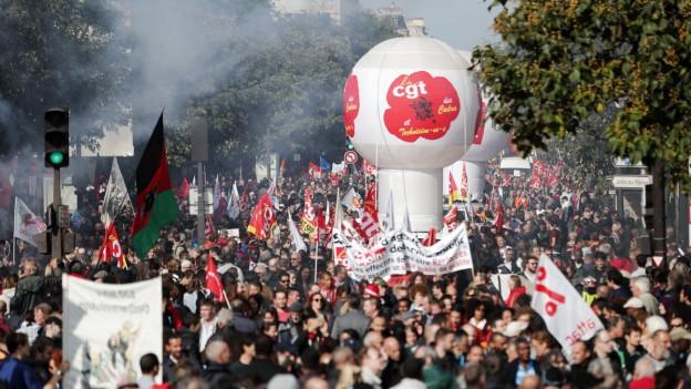Eine Strasse gefüllt mit Menschen an einer Demonstration in Frankreich.