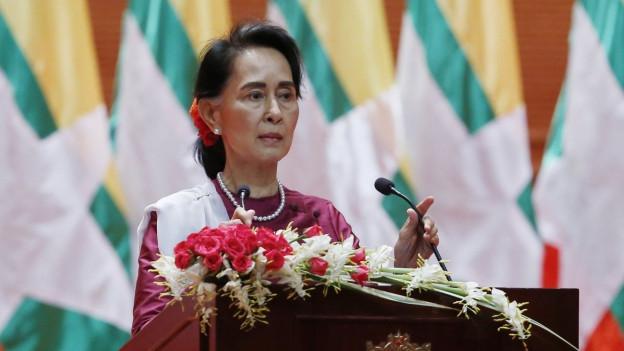 Aung San Suu Kyi mit einer Blume im Haar vor einem Pult mit Mikrofonen und Blumenbouquet darauf.