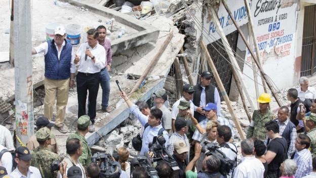 Mexikos Präsident steht auf den Trümmern eines Hauses und spricht zu den Menschen.