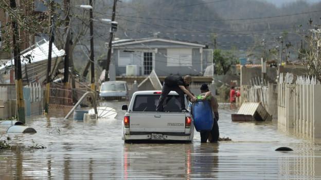 Menschen laden ihre Habseligkeiten in einen Pick-Up, der in einer überfluteten Strasse steht.