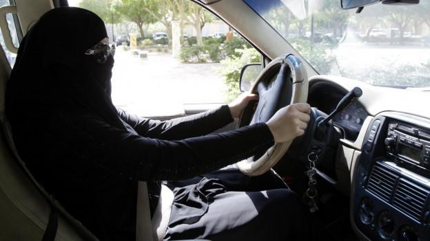 Eine schwarz verschleierte saudische Frau mit Sonnenbrille am Steuer eines Autos.