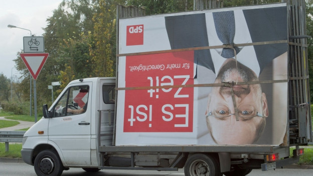 Auf dem Bild zu sehen ist ein Transporter auf dem ein Wahlplakat von Martin Schulz liegt
