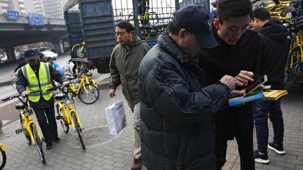 Auf dem Bild zu sehen sind zwei Männer. Einer erklärt dem anderen auf dem Smartphone wie die Velo-Miete funktioniert