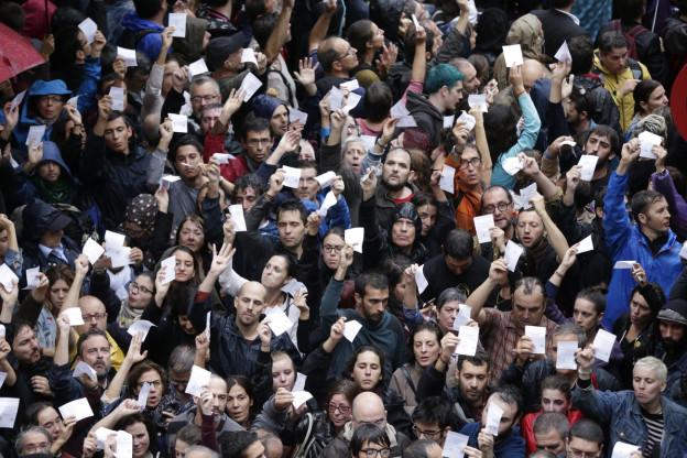 Katalaninnen und Katalanen zeigen ihre Abstimmungspapiere.