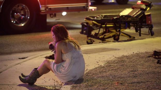 Eine Frau sitzt auf einem Bordstein nach der Schiesserei am Musikfestival in Las Vegas