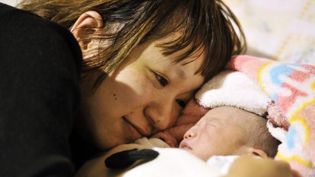 Nahaufnahme von Mutter und Neugeborenem im Wochenbett