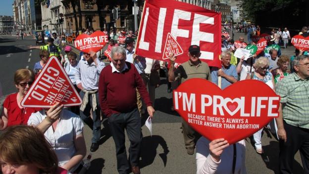 Irische Abtreibungsgegner marschieren mit roten Plakaten durch die Strassen, auf denen steht, dass sie für das Leben seien.