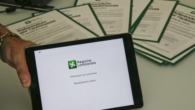 Ein ipad vor Abstimmungsunterlagen in verschiedenen Sprachen in der Lombardei.