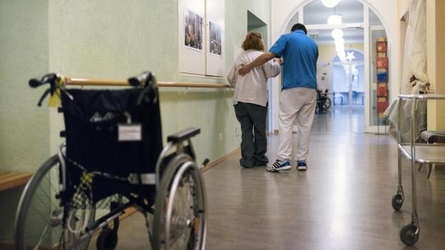 Ein Pfleger stützt eine ältere Frau.