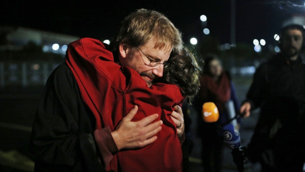 Peter Steudtner in Istanbul, schwarze Jacke und Brille, er umarmt erleichtert einen Kollegen, um sie herum stehen Journalisten.