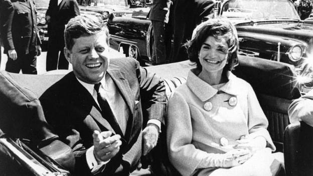 auf dem Bild zu sehen ist John F. Kennedy mit seiner Frau. In einem Auto sind sie unterwegs zu einer Veranstaltung.