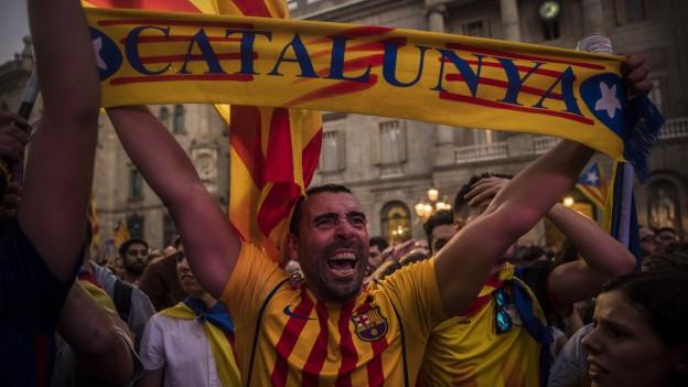 Ein Mann hält ein Banner mit der Aufschrift «Catalunya» in die Höhe.