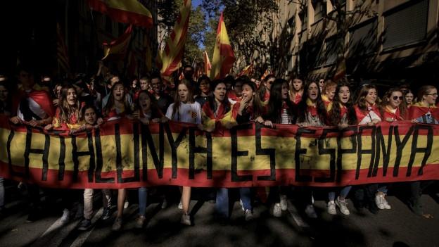 Demonstranten tragen ein Banner vor sich her mit der Aufschrift: Katalonien ist Spanien.