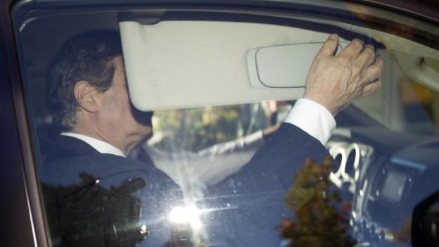 Paul Manafort verdeckt im Auto sein Gesicht vor den Fotografen.