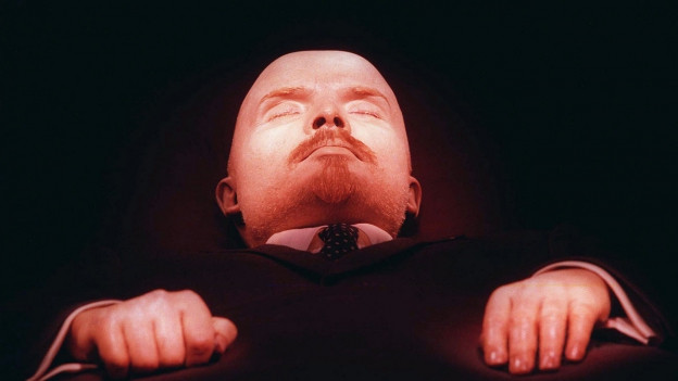 Der Kopf und die Hände der Leiche Lenins im rötlichen Licht.