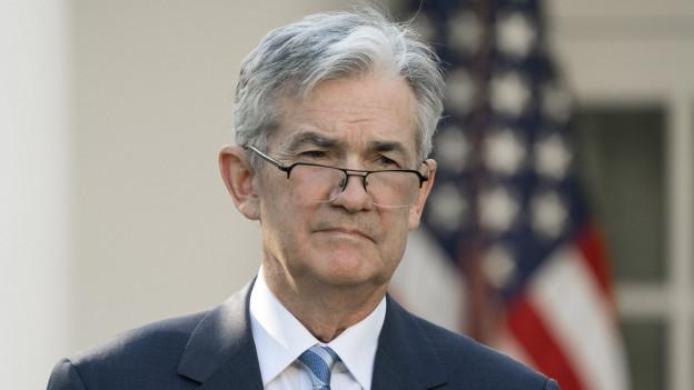 Porträt-Aufnahme von Jerome Powell, graue Haare und Brille, blau gestreifte Krawatte, hinter ihm die US-Flagge, er blickt konzentriert.