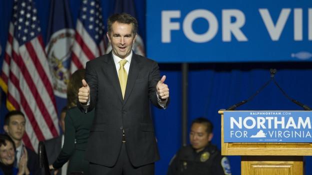Der frisch gewählte demokratische Gouverneur von Virginia, Ralph Northam, steht auf einer Bühne und streckt beide Daumen hoch. Seine Anhänger applaudieren.