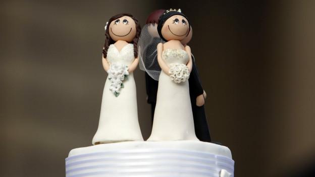 Ein Kuchen, mit zwei heiratende Frauen als Figürchen.