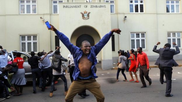 Menschen jubeln vor dem Parlament von Simbabwe.