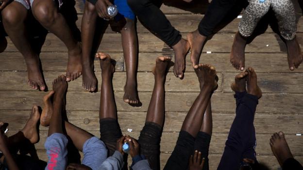 Migranten sitzen am Boden, strecken ihre Beine von sich.