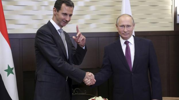 Der syrische Machthaber Assad und Russlands Präsident Putin schütteln sich die Hand.
