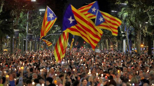 Menschen demonstrieren mit der katalonischen Separatisten-Flagge und Kerzen für die Unabhängigkeit.