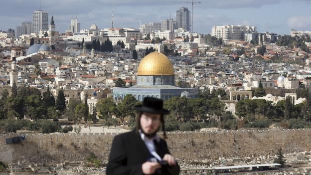 Im Hintergrund ist die Stadt Jerusalem, im Vordergrund ein orthodoxer Jude mit Hut.