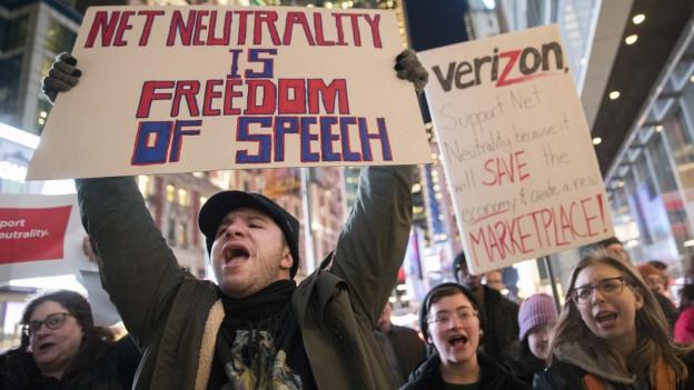 Menschen mit Plakaten demonstrieren in New York gegen den Angriff auf die Netzneutralität.
