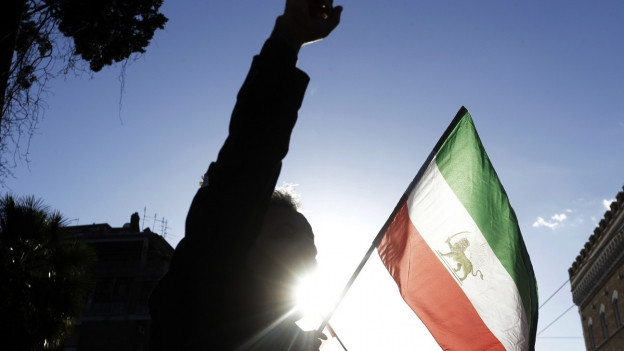 Ein Demonstrant streckt die Faust in die Höhe, neben der ehemaligen iranischen Flagge.