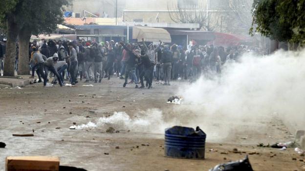 Auf dem Foto sind protestierende Bürger zu sehen, es kommt zu Ausschreitungen
