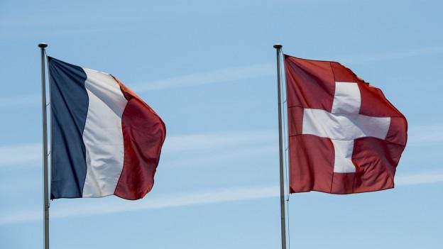 Die Flaggen von Frankreich und der Schweiz wehen im Wind.