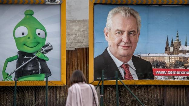 Das Bild zeigt eine Frau, die vor zwei Werbeplakaten steht. Das Plakat links zeigt ein grünes Männchen, rechts ist Tschechiens Präsident Zeman zu sehen.