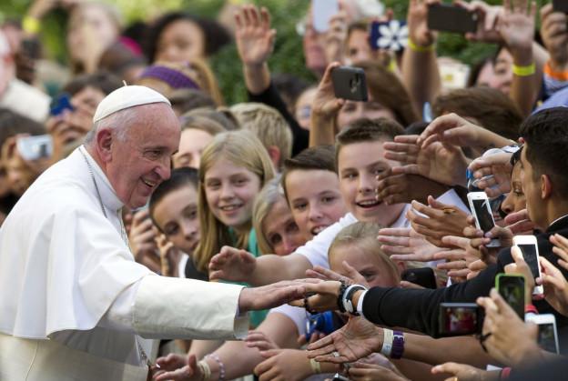 Das Bild zeigt Papst Franziskus, wie er Hände von Jugendlichen schüttelt.