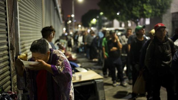 Menschen stehen Schlange für eine Suppe und ein Stück Brot in einer Suppenküche in LA.