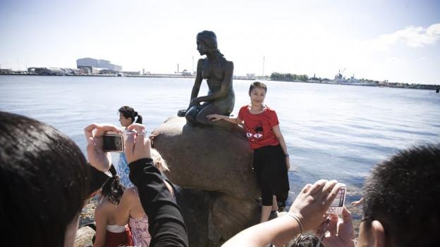 Die bekannte Statue in Kopenhagen, die Meerjungfrau am Hafen, wird von Touristen fotografiert.