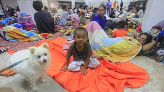 Ein kleiner Junge sitzt auf einem orangen Tuch auf dem Boden. Um ihn herum und im Hintergrund liegen viele andere Menschen auf Matten und Tüchern.