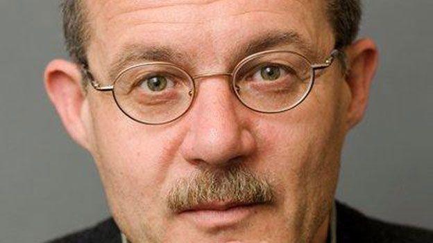 Porträt von SRF-Auslandredaktor Joe Schelbert, Brille, Schnauz und dunkle Haare, ein leichtes Lächeln auf den Lippen.