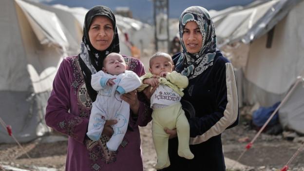 Zwei Frauen in einem türkischen Flüchtlingscamp, sie stehen nebeneinander und halten je ein Baby in die Kamera, beide Frauen tragen Kopftuch.