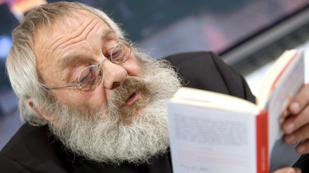 Harry Rohwohl, Brille, kurze, graue Haare, grauer Rauschebart, liest aus einem Buch.